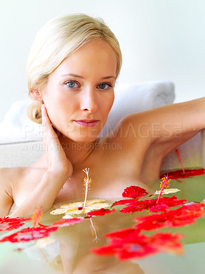 Buy stock photo Portrait of a thoughtful young woman in a bathtub with flower petals