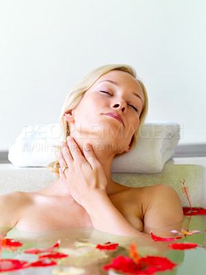 Buy stock photo Attractive blond woman taking a bath with some flower petals