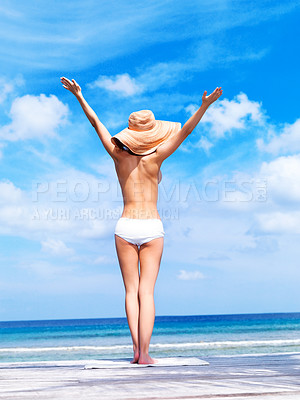 Buy stock photo Young topless woman standing on a deck with her arms raised