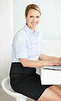 Attractive young female executive using a laptop at desk