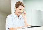 Cheerful executive talking on cellphone while using a laptop
