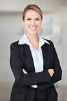Successful business woman in suit with hands folded smiling