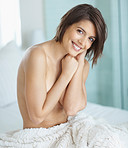 Smiling and nude in bed