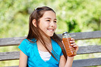Happy young girl holding a bottle of juice in a countryside