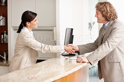 Buy stock photo Happy mature businessman shaking hands with the receptionist in the hotel lobby