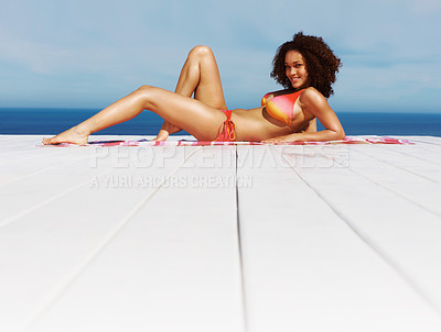 Buy stock photo Happy woman lying in a bikini on a deck floor and smiling