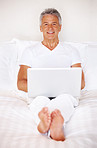 Mature man relaxing in bed with laptop