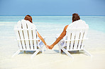 Loving couple relaxing on deck chairs