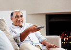 Smiling man watching TV while relaxing on a couch
