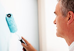 Closeup of a mature man painting a wall blue