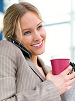Young beautiful smiling business woman talking on her cell phone and drinking coffee