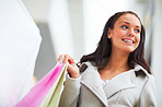 Closeup portrait of smiling young lady carrying shopping bags