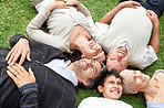 Happy family of five relaxing on grass in park