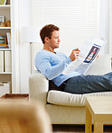 Man lying on couch reading newspaper