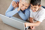 Grandson and grandmother browsing the internet on floor