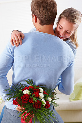 Buy stock photo Happy couple embracing with a man hiding flowers behind his back