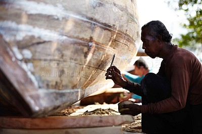 Buy stock photo Craftsman carefully working on a traditional Thai wooden boat