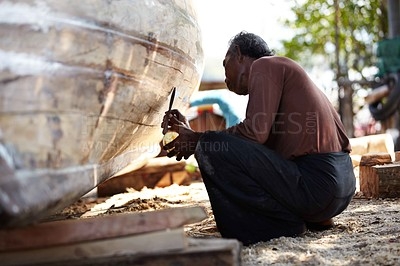 Buy stock photo A Thai craftsman repairs a traditional wooden boat - low angle