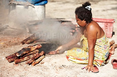 Buy stock photo A destitute Thai woman sitting on the ground tending a woodfire