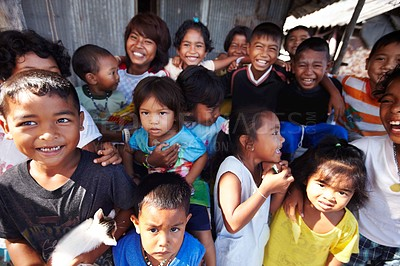 Buy stock photo A group of local children standing outside a tin shack