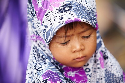 Buy stock photo A small Asian girl wearing a colorful headscarf and looking down
