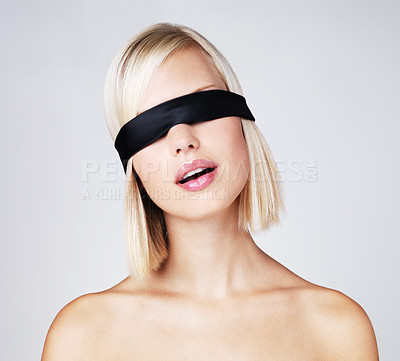 Buy stock photo Young woman isolated on grey wearing a blindfold
