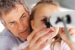 Mature father helping her daughter to look through telescope