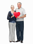 In love - Senior couple holding a heart shaped board on white
