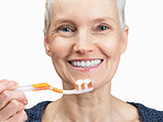 Beautiful old woman's face with a toothbrush on white