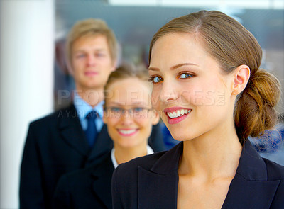 Buy stock photo Portrait of a young businesswoman standing in the office with her colleagues in the background