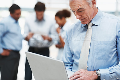 Buy stock photo Senior business man working on a laptop with coworkers in the background