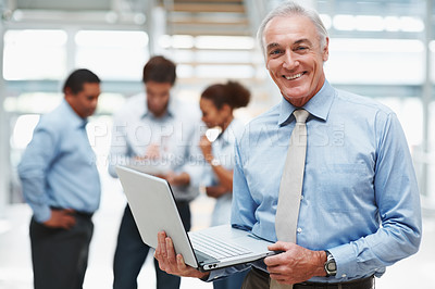Buy stock photo Happy senior business man using a laptop with colleagues at the back
