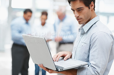 Buy stock photo Smart young executive working on a laptop with colleagues in the background - copyspace