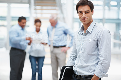 Buy stock photo Handsome young business man with a laptop and colleagues at the background