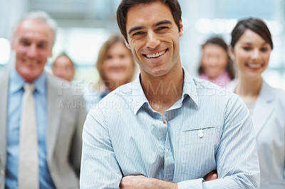 Buy stock photo Confident young business executive with his team in the background
