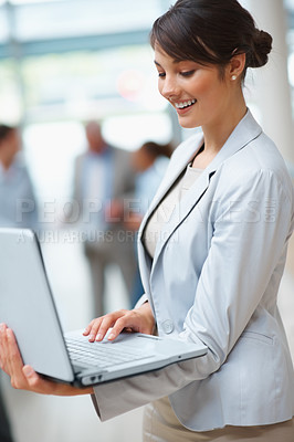 Buy stock photo Happy young business woman using laptop with colleagues in the background