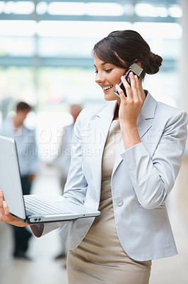 Buy stock photo Happy young business woman talking on cellphone and using laptop