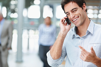 Buy stock photo Handsome young business man enjoying a conversation on his cellphone next to bright copyspace