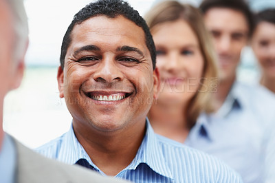 Buy stock photo Portrait of a happy mixed race business man in line with colleagues