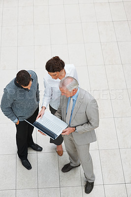 Buy stock photo Top view of three business executives discussing work on laptop