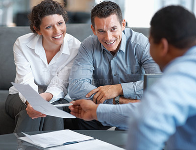 Buy stock photo Smiling young couple receiving positive advice from their financial consultant