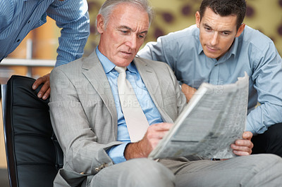 Buy stock photo Senior business man and colleagues sharing the financial newspaper