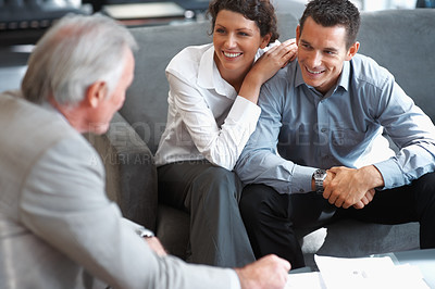 Buy stock photo Real estate agent having a discussion with a happy couple