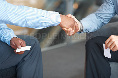 Buy stock photo Business people exchanged business cards and shaking hands over a deal