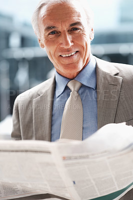 Buy stock photo Smiling senior business man reading a newspaper indoors