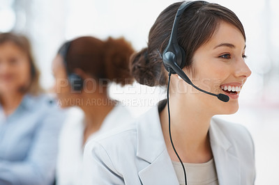 Buy stock photo Service with a smile - Closeup of a young smiling operator with headset at workplace