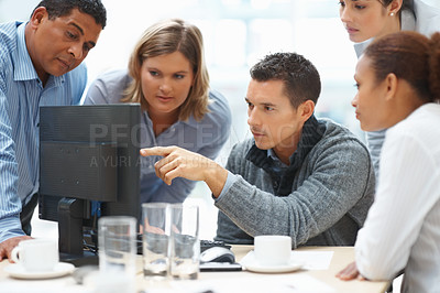 Buy stock photo Teamwork - Business man showing something on laptop screen to colleagues