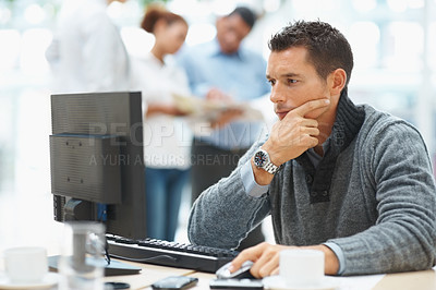Buy stock photo Smart business executive working on a computer with colleagues in the back