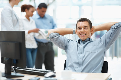 Buy stock photo Young business man relaxing at desk with colleagues in the background
