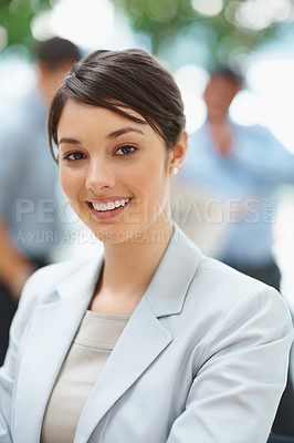 Buy stock photo Pretty smiling Caucasian business woman with colleagues in the background